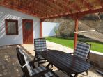 Covered veranda with sea view, hammock and dining table, coffee table, loungers