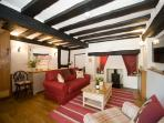 The cosy sitting room of Daisy Cottage with the original oak beams dating back to 1571