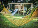 Backyard space with a hammock and kid play area.