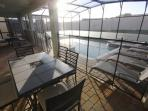 Screened in lanai with plenty of patio furniture and seating