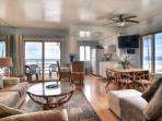 Living room, dining area, kitchen, view of patio and beach views.