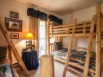Twin over full and twin over twin pine bunk beds in bedroom 3. View of private deck access.