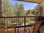Deck, with breathtaking view of the creek, furnished with seating for two and gas grill.