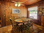 Dining area (in cabin) has tongue and groove walls and tiled floors.