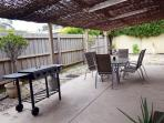 Outdoor entertainment area, with BBQ area and outdoor setting.