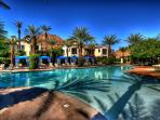 Family pool area with beach style entry, cabanas, fountains, and kids' splash pad.