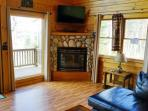 Open living room area with fireplace - Brassua Lake Log Cabin