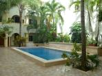 Tranquil swimming pool surrounded by tropical gardens.