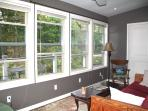 sitting room windows overlook the wooded pond area in the back