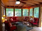 Huge front screened in porch with seating and additional dining area