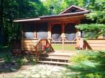Welcoming entrance to cabin and screened in front porch area
