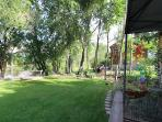 summer view of yard with river in the distance and owner's home next door