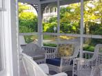 A large screened in porch with lots of cushioned seating. A great place to enjoy the ocean breezes!