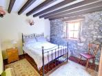 The ground floor double bedroom has a beamed ceiling and feature stone walling to one side