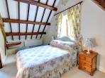 The pretty double bedroom has interesting beams in a steeply sloping ceiling