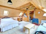 The main room is a spacious bed-sitting room, with double bed, futon sofa and folding armchairs