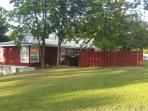 Private  parking just by the red fence.  Guest room just down the stairs.  Gorgeous shade trees