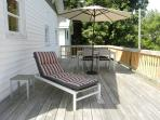 Another view of the deck featuring comfortable sun lounger.  Steps from deck lead down into yard.