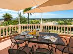Dining terrace with views of the golf course and the sea