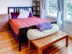 The bedroom hosts a cozy queen bed.
