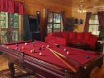 Game room with stand-up arcade unit, pool table, and sectional sofa.
