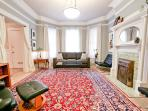 Living Room with Queen-size SofaBed and Recliner. Oriental Carpets. Period Details. Original Artwork