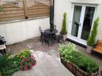 Dining area in garden with patio table and umbrella, gas BBQ.