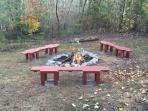 Fire pit with benches in the private back yard.
