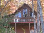 Front view of chalet style cabin.  Surrounded by beautiful foliage.