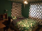 downstairs queen bed with desk, executive chair, and tv