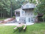 Side patio offers compact firepit with numerous chairs and picnic table