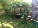Backyard sitting area with grape arbor, gas grille and outdoor shower