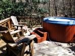 The hot tub sits on the back deck above the creek, offering serene views