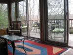 enclosed porch leads to upper outdoor deck with barbecue grill