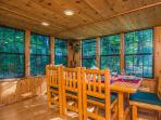The dining room is surrounded by windows on 3 sides with glorious wooded views