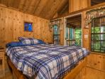 You'll sleep well in this comfortable master bedroom with whimsical stained glass window