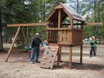 Kids love to play on the swing set in common area in front of our cabin, Whispering Pines Lodge.