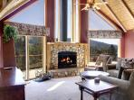 Great Room with wood burning fireplace and two-story windows with endless views