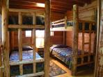 Bunk Room.  Four twins on hand made log bunks and hand made quilts.