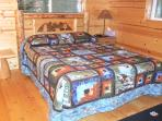 Main level Queen Bedroom. Log furniture and hand made quilts.