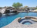 The pool with rock waterslide and swim up bar.