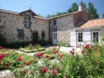 Façade du Gîte du Vieux Château, ensoleillée et fleurie côté cours pavée exposée sud est.
