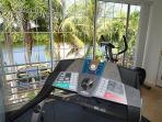 indoor gym with dry sauna, overlooks pool and canal. Sliding windows open fully