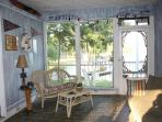Screen porch has a gas grill and ceiling fan for a relaxing place to gather.