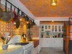 kitchen with hanging copper pots and pans, painted armoire with dishes and pottery