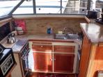 Kitchen with range, oven, double sink, microwave, and refrigerator