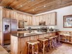 Gourmet kitchen features granite counters, tiled floors, breakfast bar and stainless steel appliances - fridge...