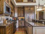 The gourmet chef's kitchen is tastefully finished with custom cabinetry, Viking stainless steel appliances, granite...