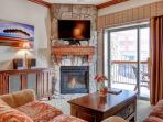 Living room with floor to ceiling stone fireplace, large flatscreen HDTV and private balcony / outdoor space.