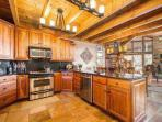 Gourmet kitchen with stainless steel appliances, custom cabinetry and granite counters. Opens up into the large family...